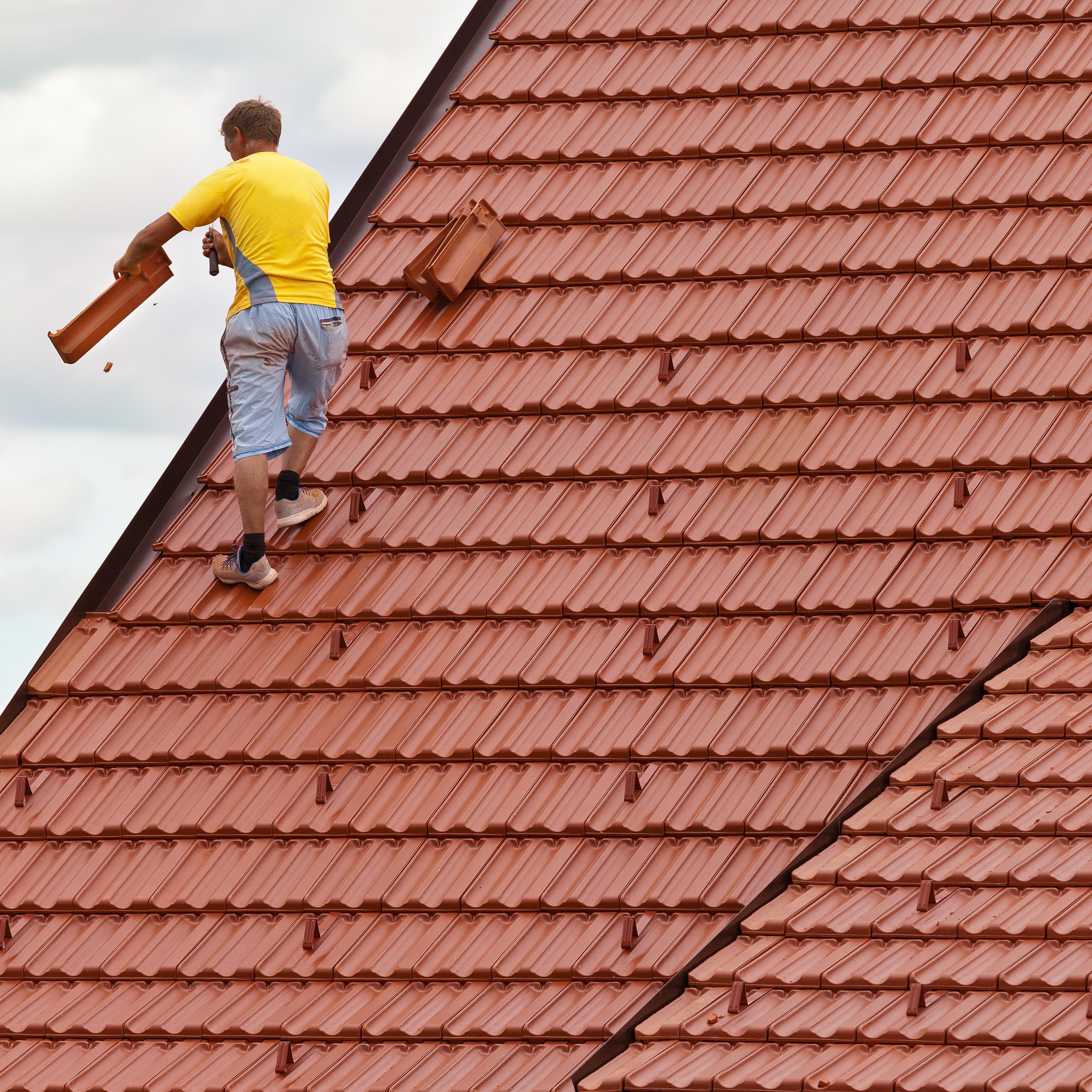 A roofer removing broken roof materials.