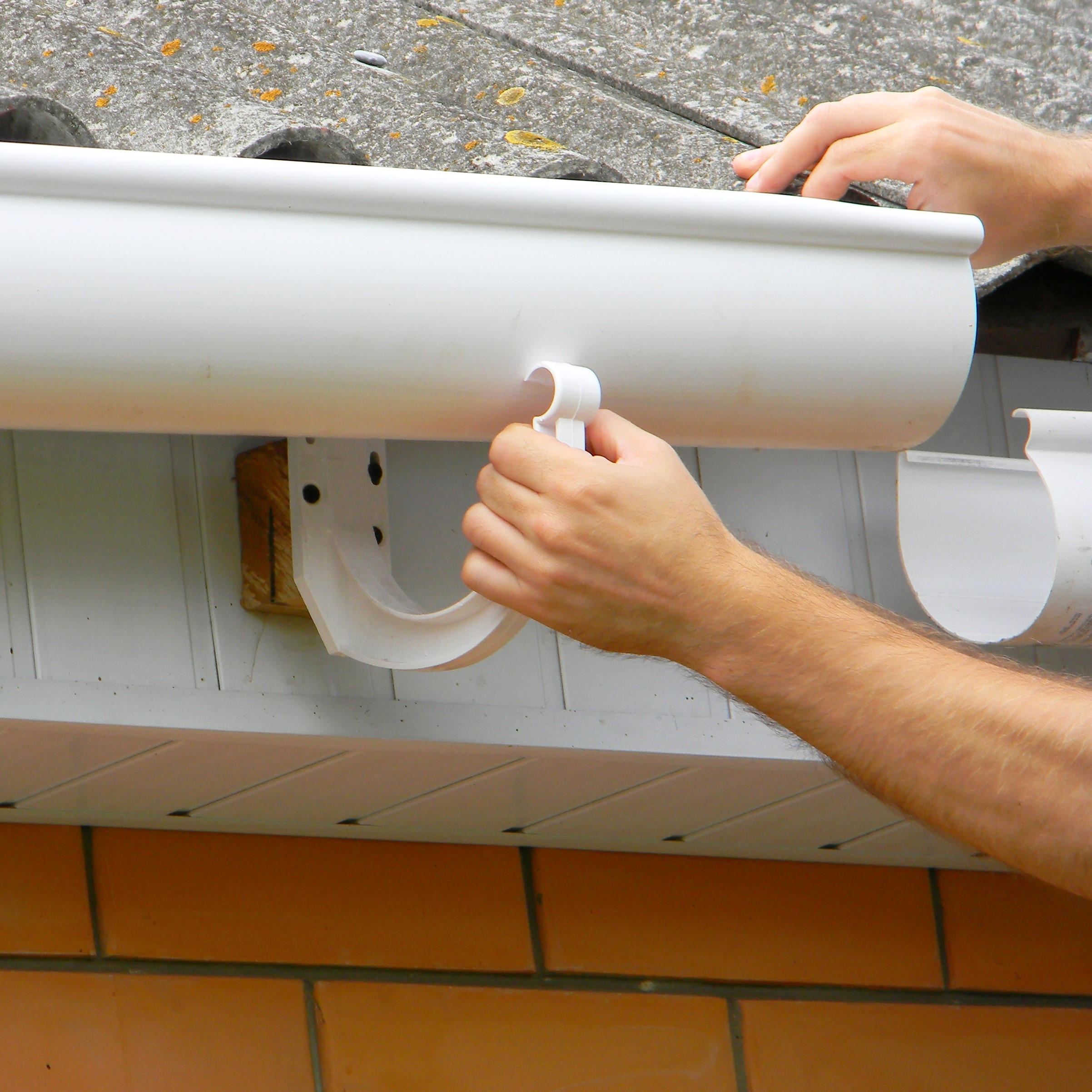A contractor fixing a gutter.