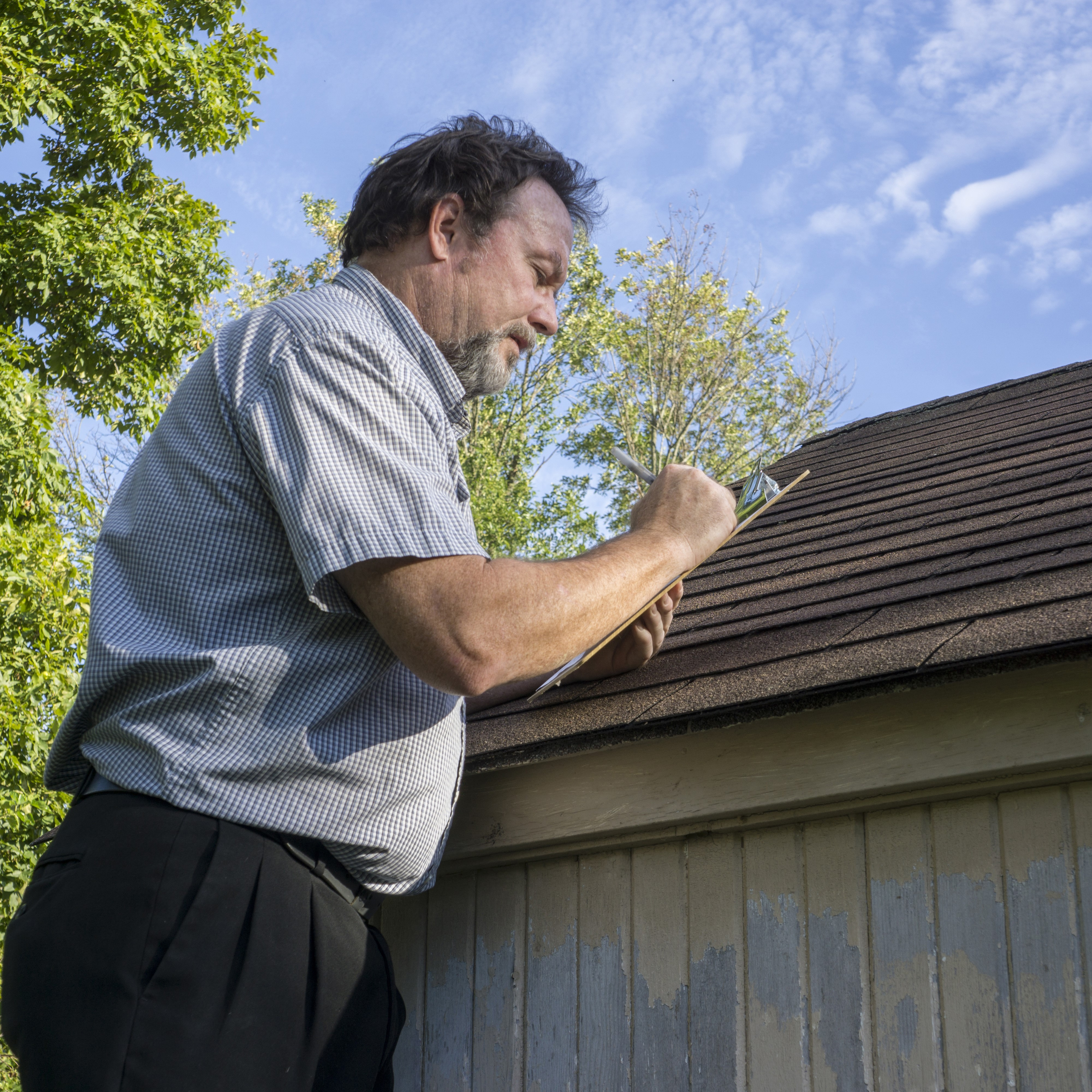 A roofing contractor inspecting a roof.